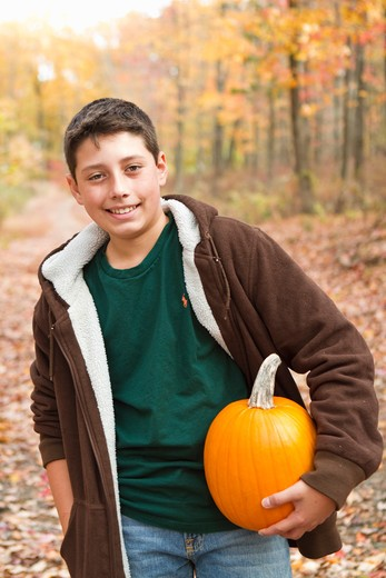 Portrait of boy carrying pumpkin in forest : Stock Photo