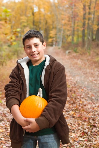 Stock Photo: 4113R-194B Portrait of boy carrying pumpkin in forest