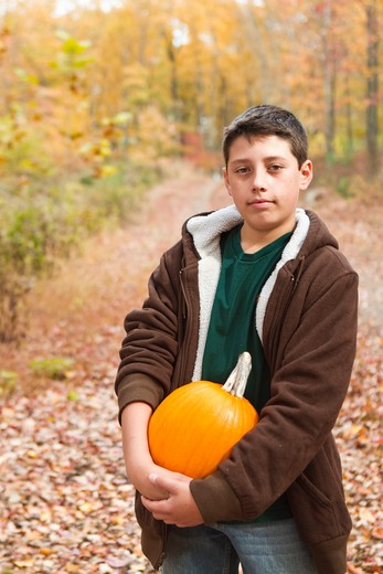 Stock Photo: 4113R-194C Portrait of boy carrying pumpkin in forest