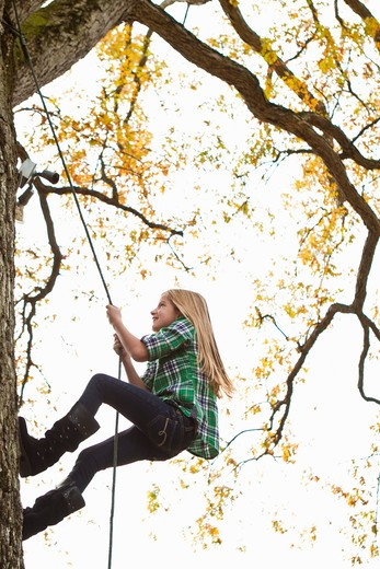 Stock Photo: 4113R-195C Girl climbing up tree