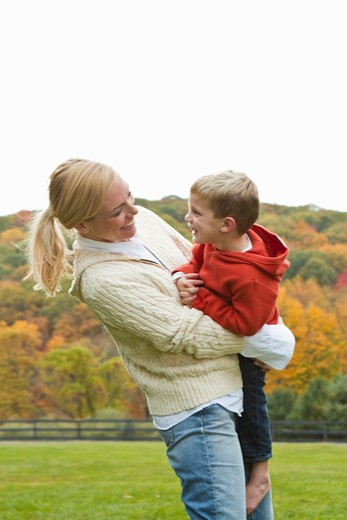 Mother playing with son on field : Stock Photo