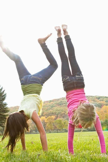 Two girls doing handstand in field : Stock Photo