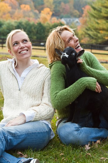 Stock Photo: 4113R-198B Two women with black lamb sitting on field
