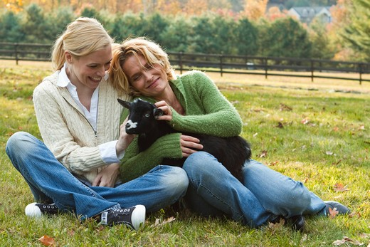 Two women with black lamb sitting on field : Stock Photo