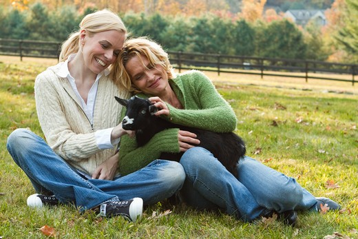 Stock Photo: 4113R-198E Two women with black lamb sitting on field