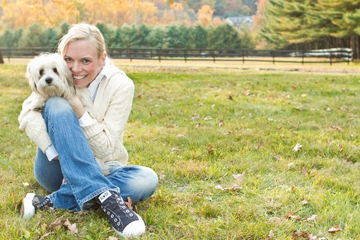Portrait of woman with white dog sitting on field : Stock Photo