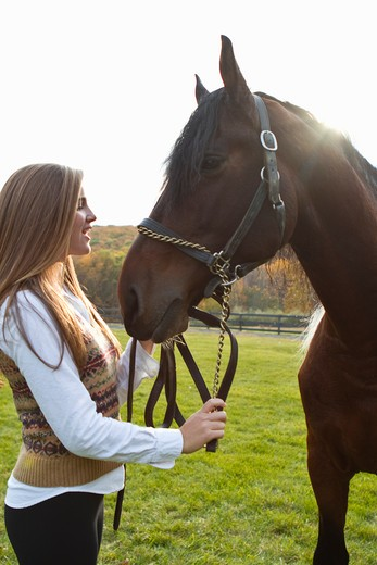 Stock Photo: 4113R-200B Teenage girl with horse on field