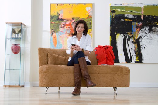 Mature woman sitting on sofa and text messaging in art gallery : Stock Photo