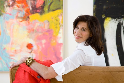 Stock Photo: 4113R-217 Mature woman sitting on sofa in art gallery