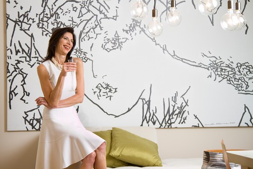Stock Photo: 4113R-222 Mature woman drinking champagne in art gallery