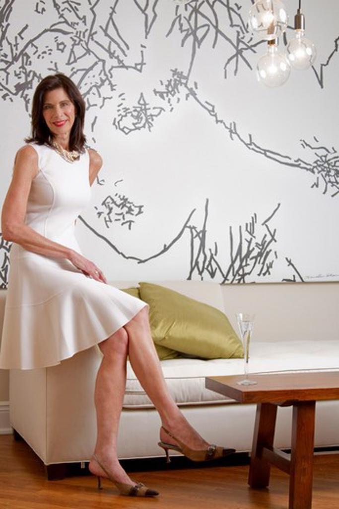 Stock Photo: 4113R-224B Mature woman sitting on sofa in art gallery