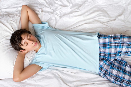 USA, New York City, Manhattan, Boy lying on bed : Stock Photo