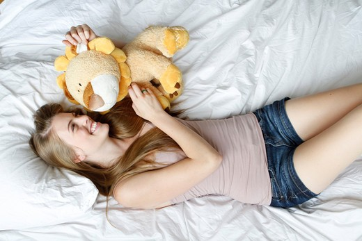USA, New York City, Manhattan, Young woman lying on bed with toy : Stock Photo