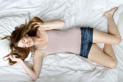 Portrait of young woman lying on bed : Stock Photo