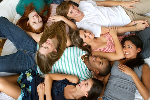 USA, New York City, Manhattan, Group of Teenage friends lying on bed : Stock Photo