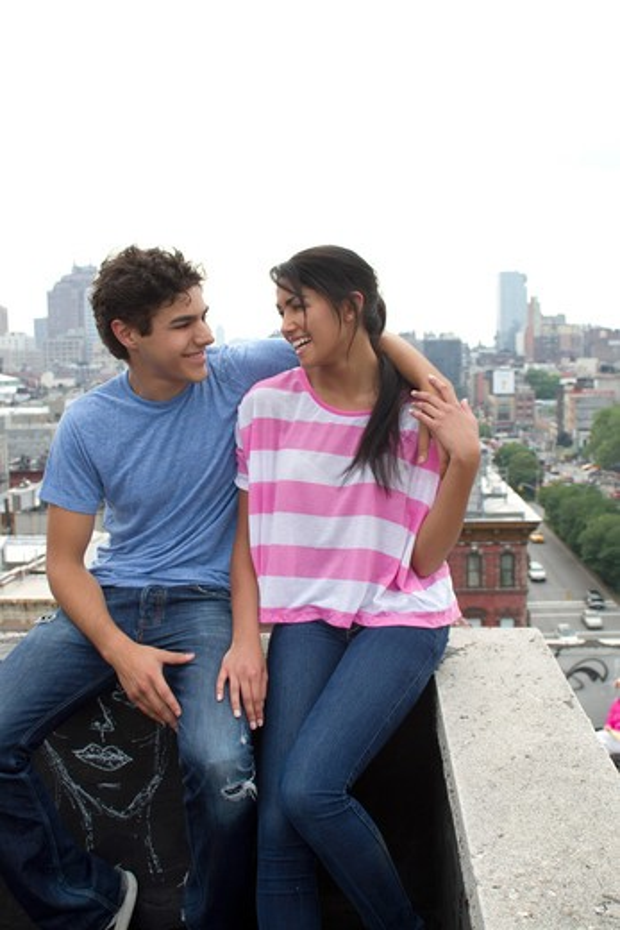 Teenage couple embracing on rooftop : Stock Photo