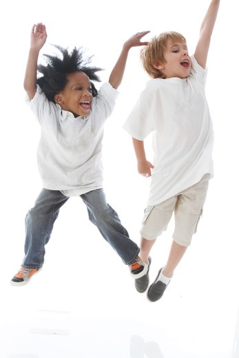 Studio shot portrait of boys jumping and laughing : Stock Photo