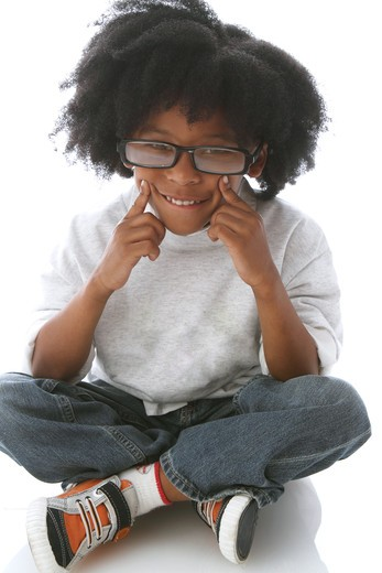 Studio shot portrait of boy with glasses seating and smiling : Stock Photo