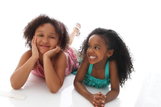 Stock Photo: 4113R-301 Studio shot of two girls lying on front and talking
