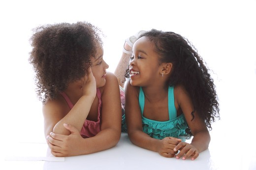 Stock Photo: 4113R-302 Studio shot of two girls lying on front and talking
