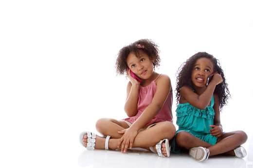 Studio shot of two girls sitting and talking on mobile phones : Stock Photo