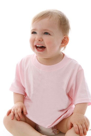 Studio shot of girl in diaper seating on floor looking away : Stock Photo