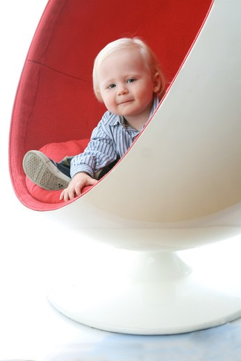 Stock Photo: 4113R-305 Studio shot of boy seating in red and white chair