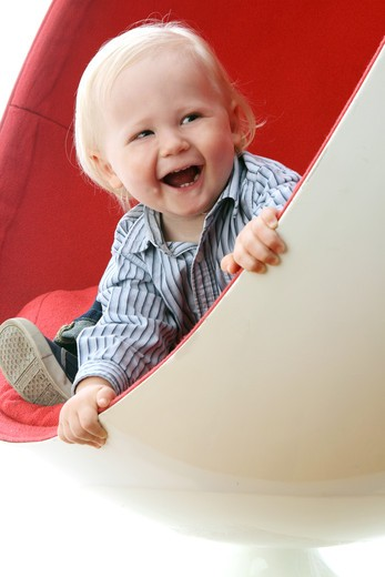 Stock Photo: 4113R-306 Studio shot of boy seating in red and white chair, laughing