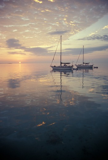 Two sailing boats at sunrise on a calm morning. The Bahamas, Caribbean, January 1997. : Stock Photo