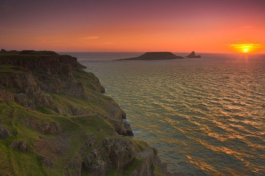 Sunset over Worms Head, Rhossili Bay, Gower Peninsula, West Glamorgan, South Wales, UK : Stock Photo