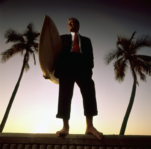 Stock Photo: 4115-1445 Businessman with surfboard on a Fort Lauderdale beach, Florida 1998. (Model released)