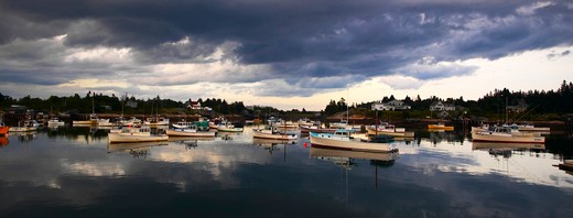 Stock Photo: 4115-1522 Heavy grey clouds reflecting around the boats moored in the harbour, Maine, USA.