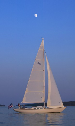 A Sparkman & Stephens designed Morris 36 sailing under the late afternoon sun with a full moon high above, Maine, USA : Stock Photo