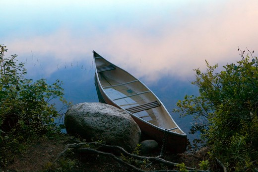 Stock Photo: 4115-1569 A kayak floating in the misty early morning light on Lake Dennison, Massachusetts, USA.