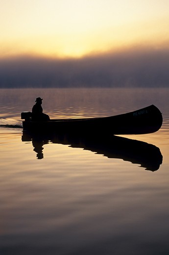Silhouette of a Wheaton canoe motoring on Big Lake, Grand Lake Stream, Maine, USA, October 1993. : Stock Photo