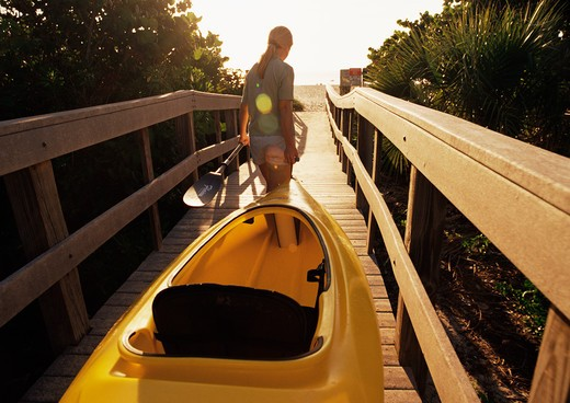 Stock Photo: 4115-1952 Woman taking her kayak and oar along the boardwalk at Vero Beach, Florida, usa 2003.