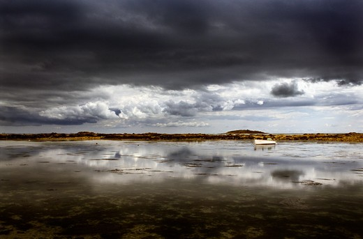 Dark clouds over a small boat off Etel in Morbihan, France. : Stock Photo