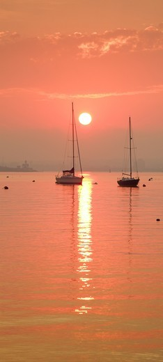 Orange sunrise over two sailboats in Jamestown Harbour, Jamestown, Rhode Island, USA. : Stock Photo