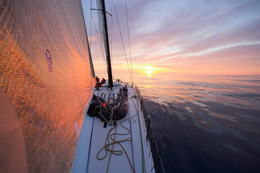Stock Photo: 4115-2063 The orange sunrise reflecting on the head sail of 'Maximus'  during the 2006 Newport to Bermuda race