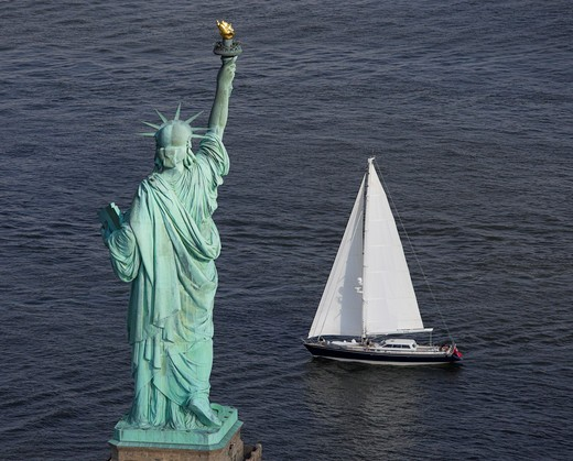 Rear view of the Statue of Liberty with a sailing boat in front, New York harbour, USA. : Stock Photo