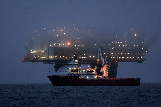 The Statfjord Bravo production platform at dusk shrouded in mist with the dive support vessel Skandi Carla undertaking subsea operations in front, North Sea, September 2006 : Stock Photo