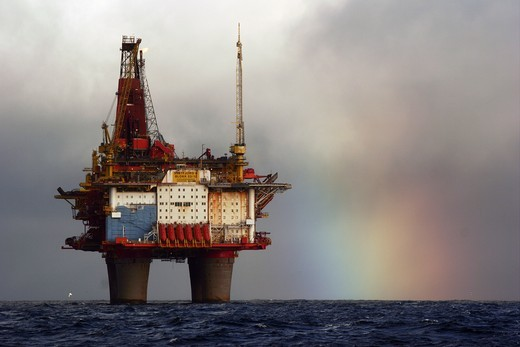 A rainbow forms behind the Statfjord Bravo production platform in the Norwegian section of the North Sea, September 2007 : Stock Photo