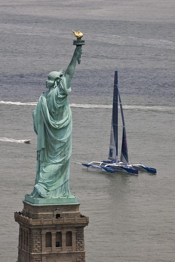 Maxi trimaran 'Banque Populaire V', skippered by Pascal Bid?gorry, arriving in Manhattan, New York, for North Atlantic record attempt. Passing the Statue of Liberty, 27 June 2009. : Stock Photo