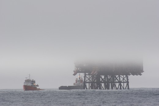 Stock Photo: 4115-3117 Piper oil field with ships in foggy conditions, North Sea. March 2005.