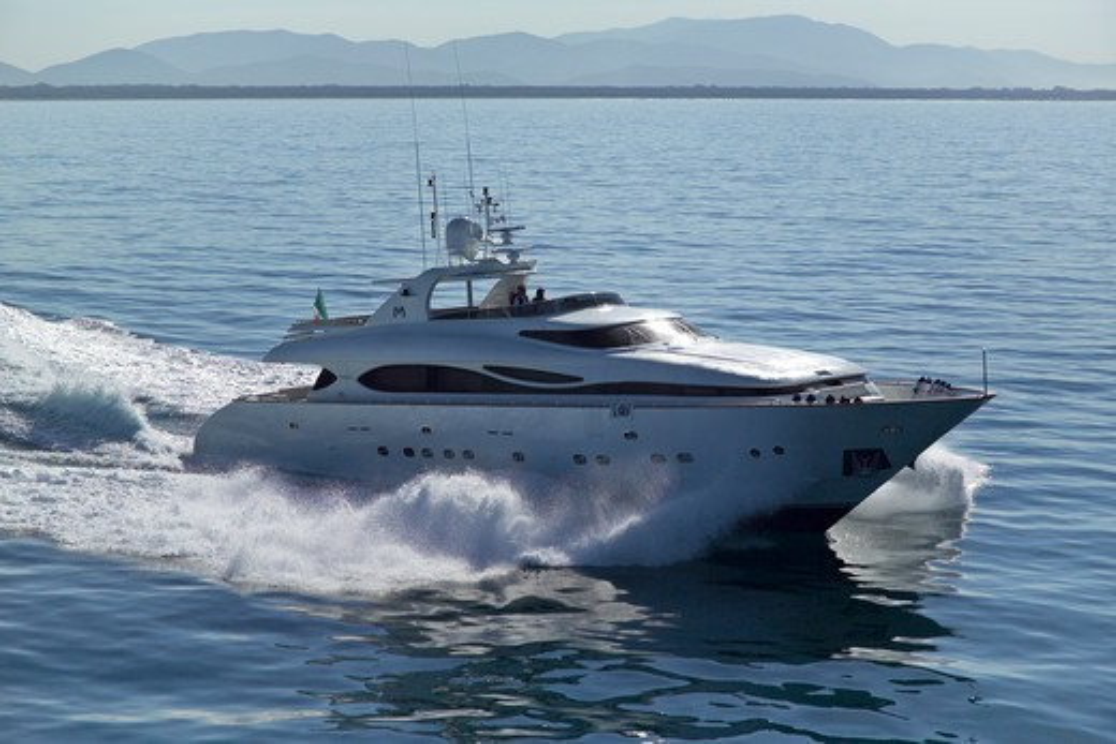 Luxurious 35-metre Gaia motoryacht, a model from the Cantieri Maiora boathouse, cruising along the mountainous coast of Viareggio, Italy. : Stock Photo