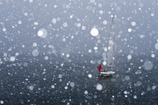 Stock Photo: 4115-3754 Sailing Laser in snow. Sweden, December 2009.