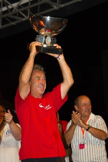 Stock Photo: 4115-3975 Monocoque 60 'Veolia Environment' skipper Roland Jourdain raising trophy as winner of Route du Rhum IMOCA Class. Guadeloupe, November 2010. Editorial use only.
