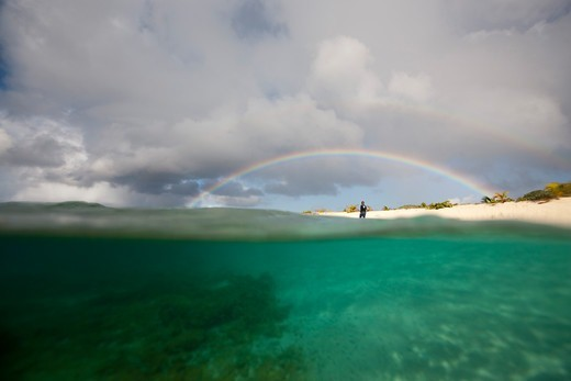 Figure beneath rainbow on Sandy Island, near Carriacou Island, the Grenadines, Caribbean, January 2010. : Stock Photo