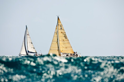 Two yachts obscured by glistening wave during the Grenada Sailing Festival, Caribbean, January 2010. : Stock Photo