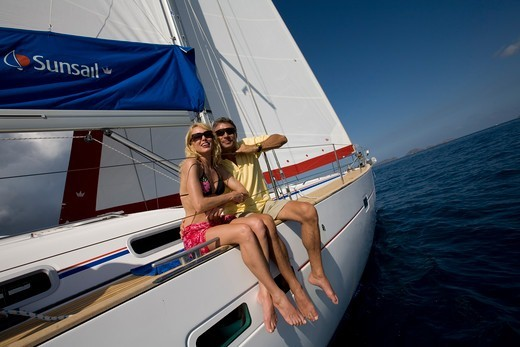 Stock Photo: 4115-4633 Couple relaxing on the rail of a Sunsail yacht in the British Virgin Islands, March 2006. Model and property released.